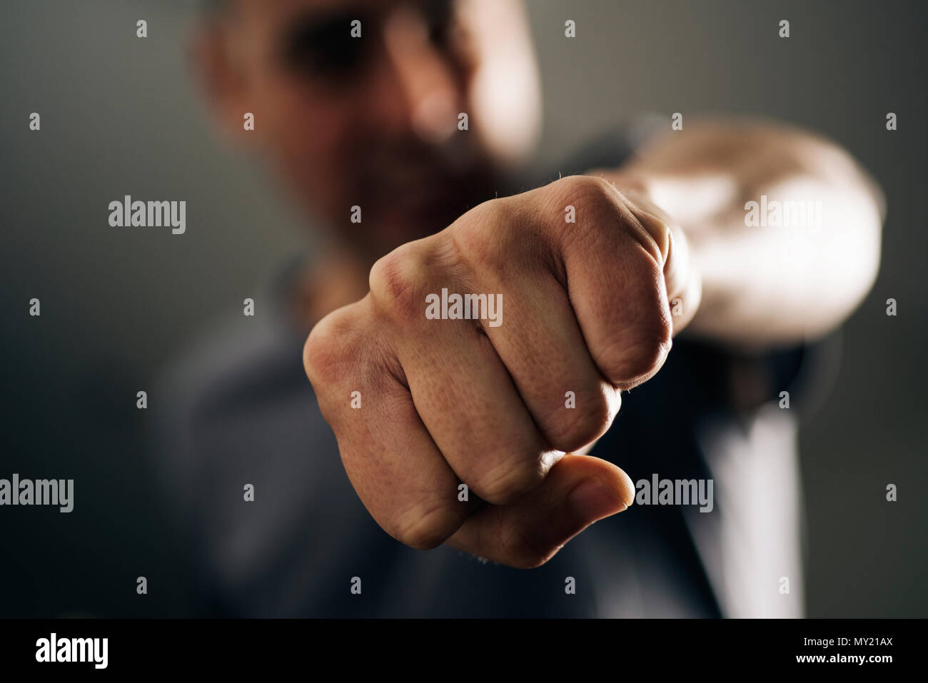 closeup of a young caucasian man throwing a punch to the observer, with a dramatic effect - Stock Image