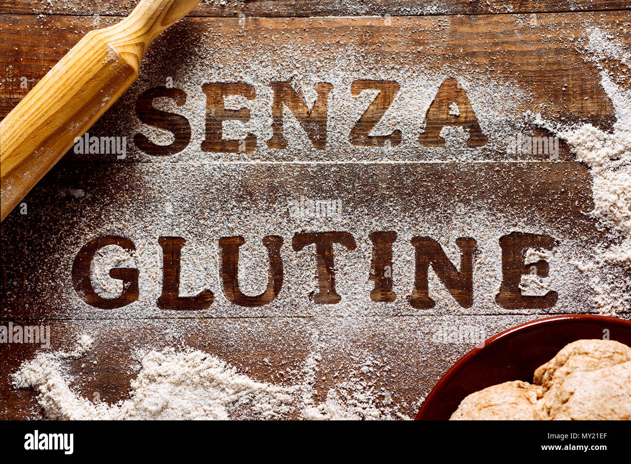 high angle view of a wooden table sprinkled with a gluten free flour where you can read the text senza glutine, gluten free in italian, next to a roll - Stock Image