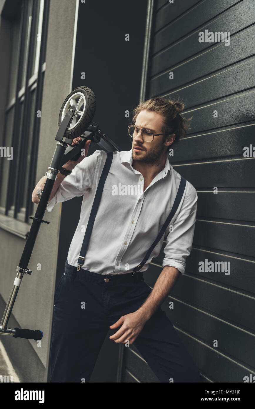 Stylish young man in spectacles and suspenders holding scooter while standing outside modern building - Stock Image