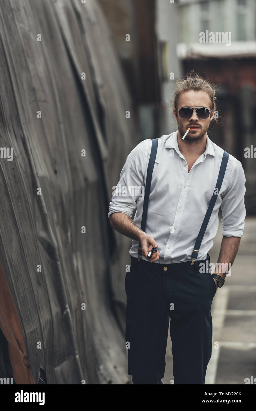 e2bc040e2d6ff Stylish young man smoking cigarette and holding lighter while walking with  hand in pocket - Stock