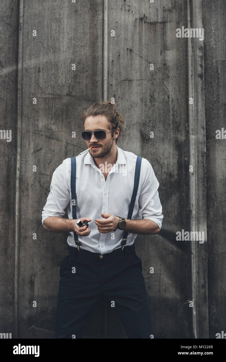 2f903520b23ef Stylish confident young man smoking cigarette and holding lighter - Stock  Image