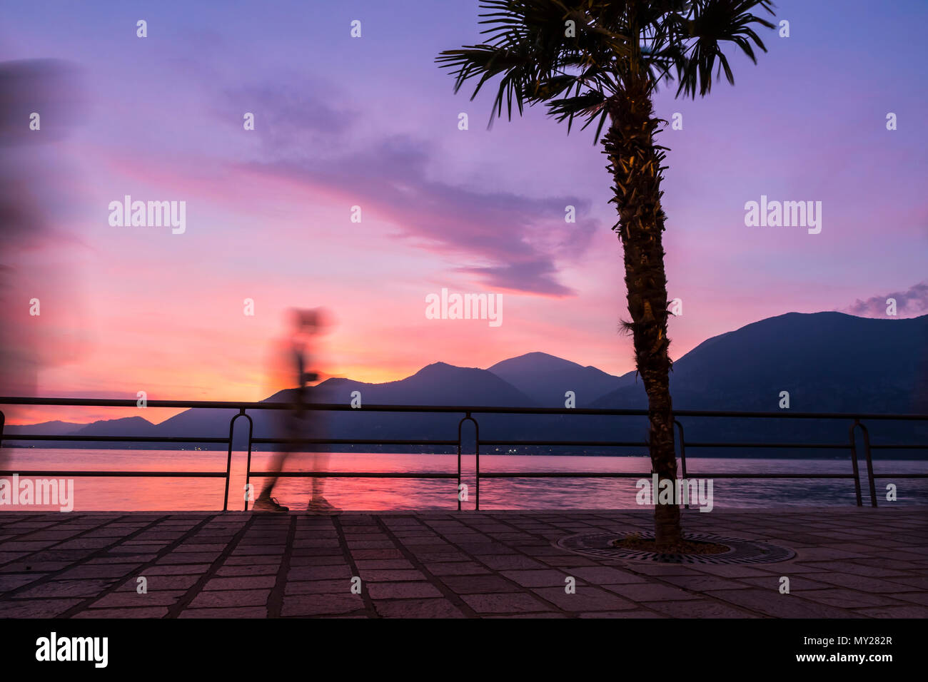 Beautiful foggy sunset at Iseo lake, Lombardy, Italy. Silhouettes of people walking on promenade street in Iseo city. Famous Italian resort - Stock Image