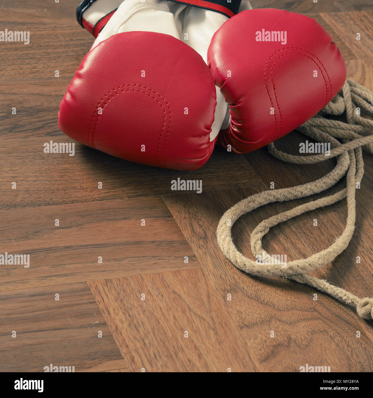 Red boxing gloves and skipping rope on a rustic wooden floor in a gym, sports or assertiveness concept - Stock Image