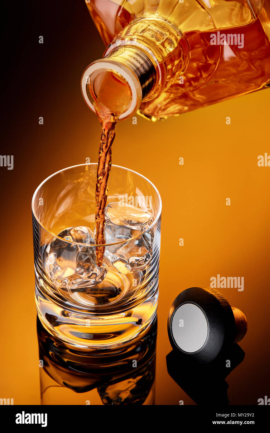 Whiskey pouring from a bottle to a whiskey glass with ice. Cap is on the table. Moody close up shoot. Stock Photo