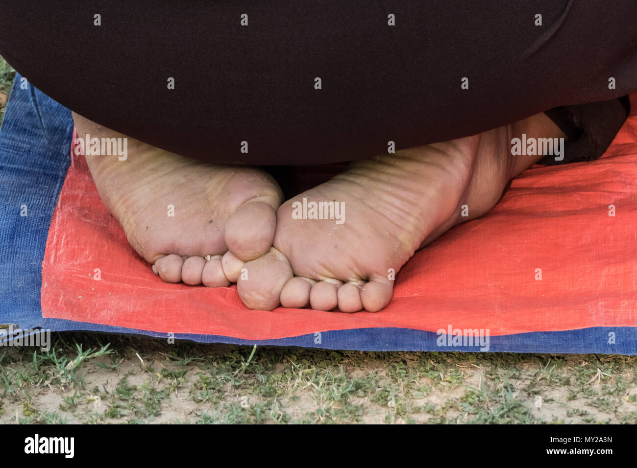 Close-up view of the bare feet of a kneeling worshipper - Stock Image