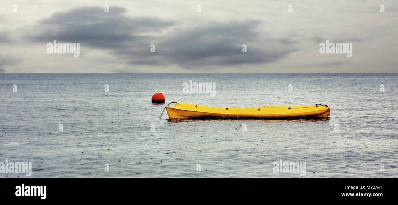 Yellow canoe and a red float on the sea on a cloudy and rainy winter day - Stock Image