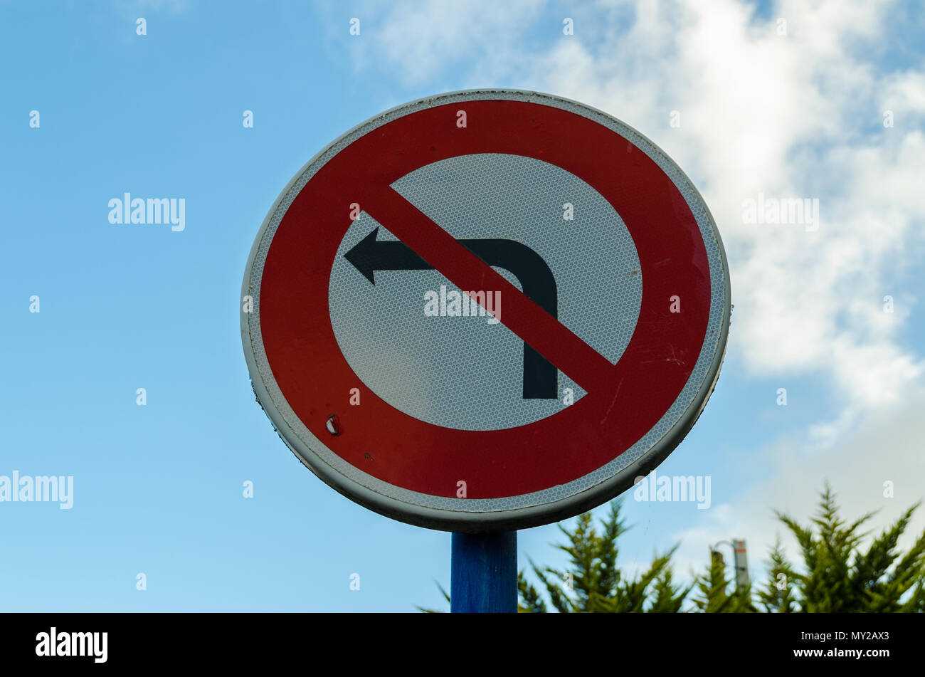 A circular road sign which prohibits vehicles from making left turns. - Stock Image