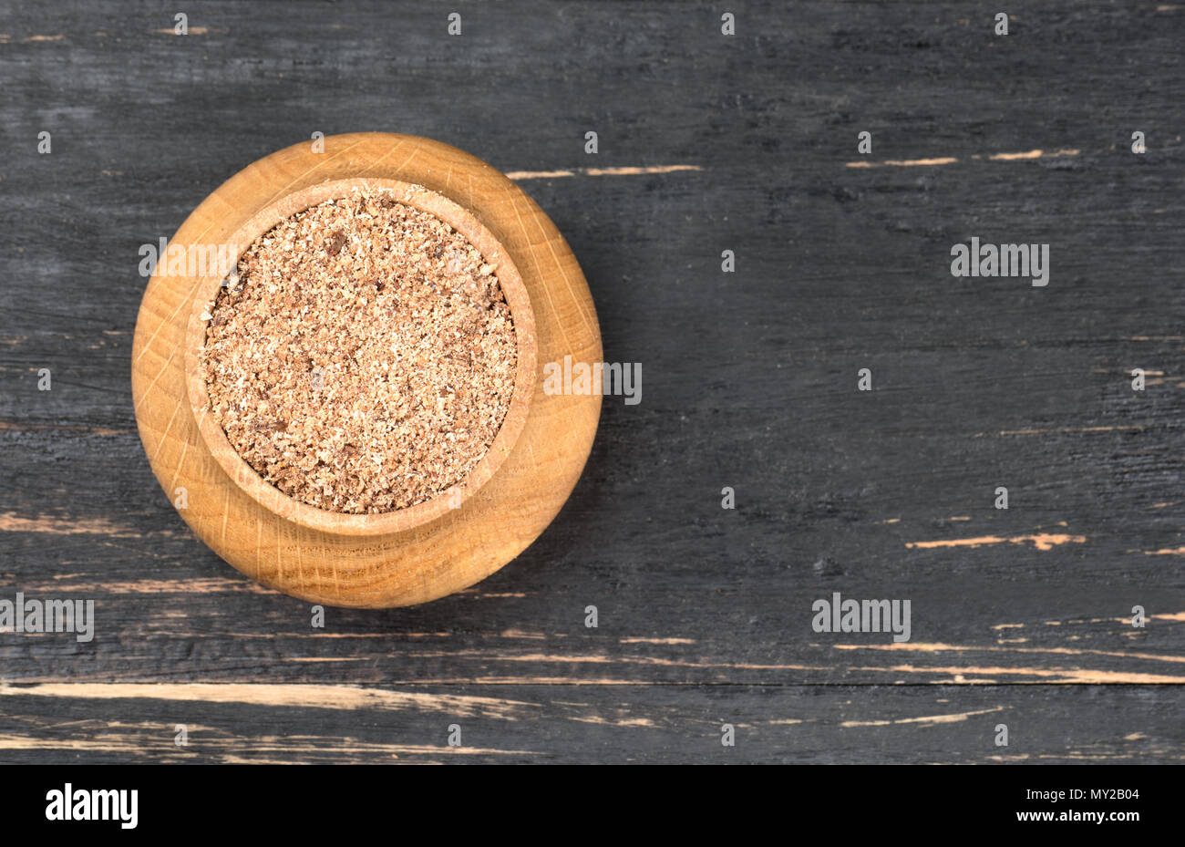 Jar with nutmeg powder on an empty wooden background, top view - Stock Image