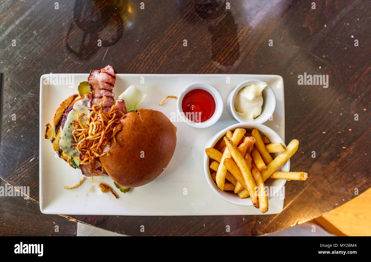 Typical British pub food: Cheeseburger with bacon and French fries (chips) with tomato ketchup and mayonnaise dips served on a white plate - Stock Image