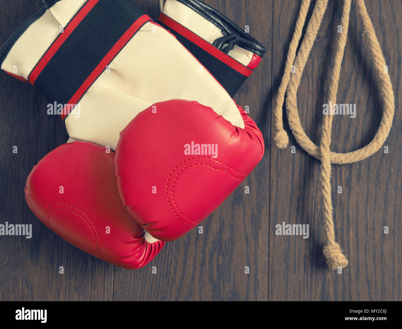 Red boxing gloves on a rustic wooden wall, sports or assertiveness concept - Stock Image