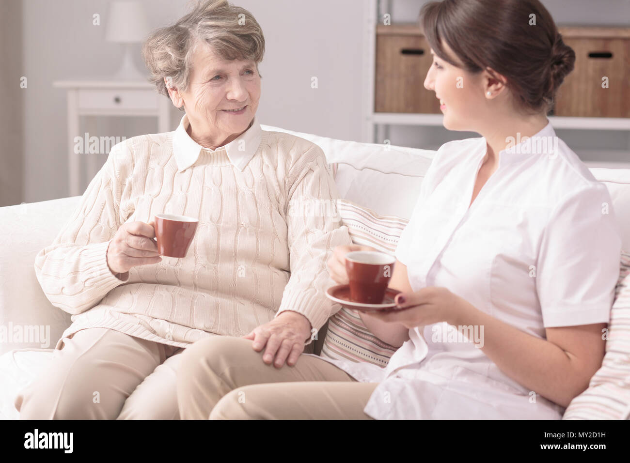 Elderly woman and her private carer sitting together on a sofa, drinking tea at home - Stock Image
