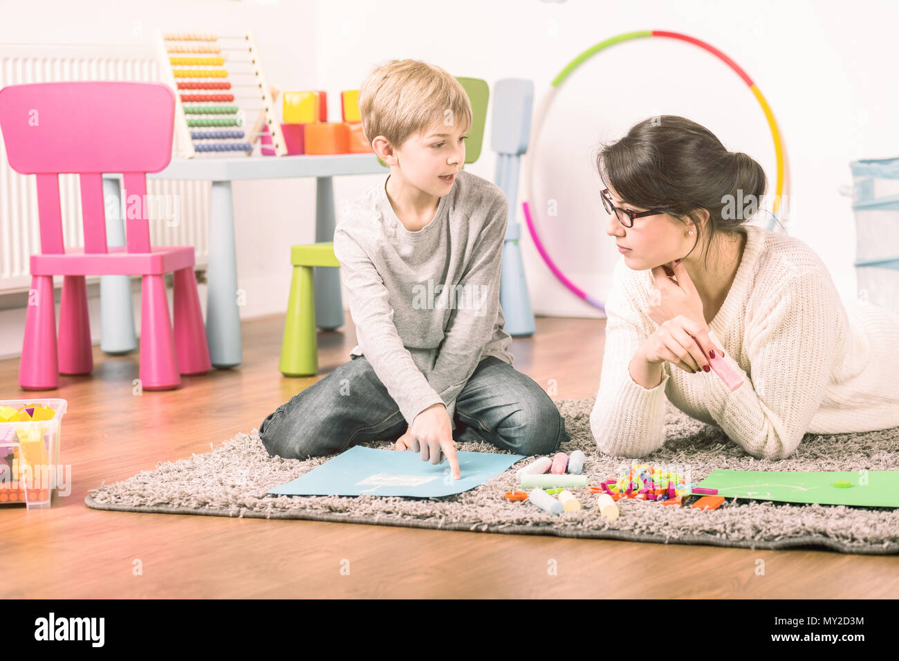 Private tutor and a small boy learning and playing at home. Fun teaching concept - Stock Image