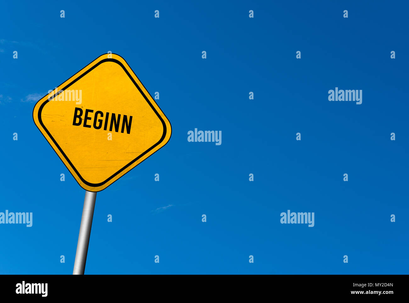 beginn - yellow sign with blue sky Stock Photo