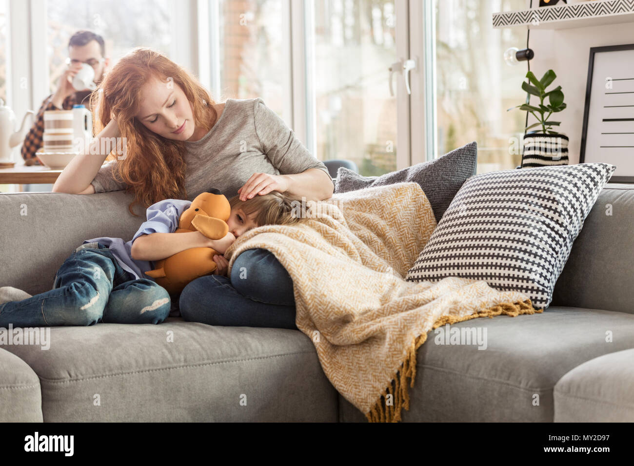 Mother taking care of her sleepy child while sitting on a couch in the living room Stock Photo