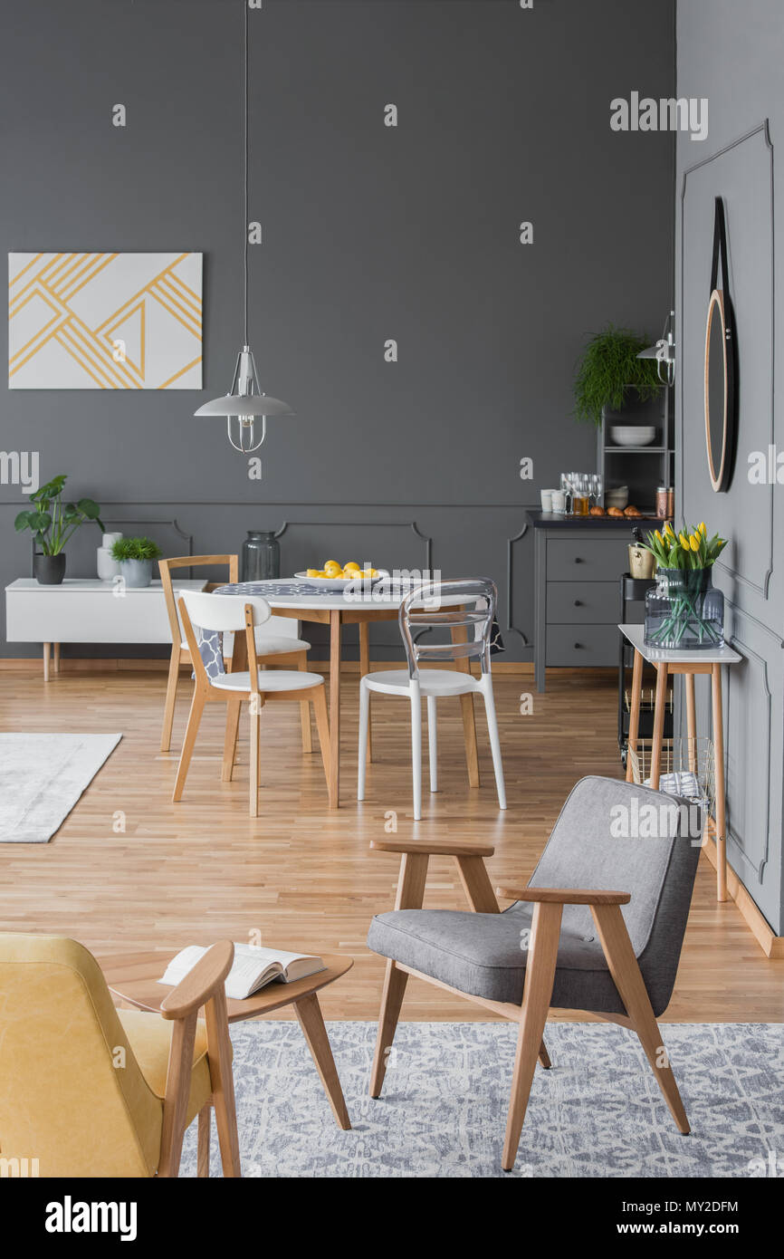 Grey And Yellow Armchair In Apartment Interior With Wooden Dining