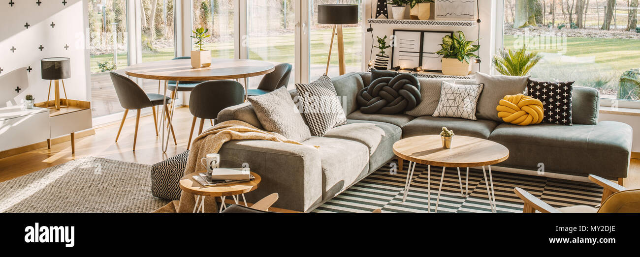 Side angle of a corner sofa with pillows and dining table with chairs behind in a bright living room interior - Stock Image