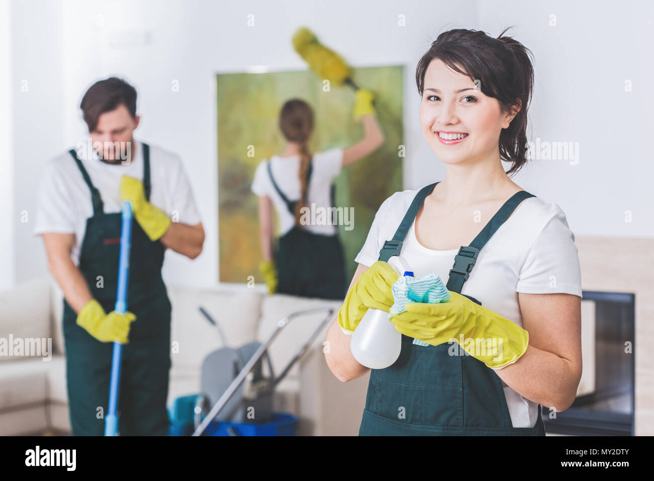 Group of young, hard-working professional cleaners in dirty apartment. Woman with cleaning solution and cloth against blurred background - Stock Image