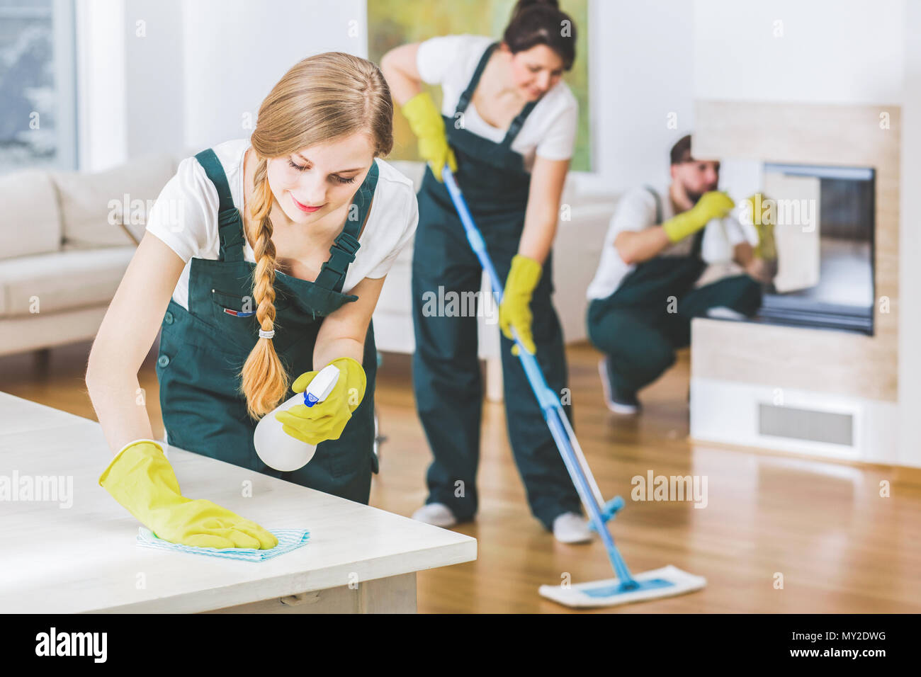 Young member of a cleaning crew wearing green overalls and yellow gloves wiping a white table in apartment interior with the rest of the team in blurr - Stock Image