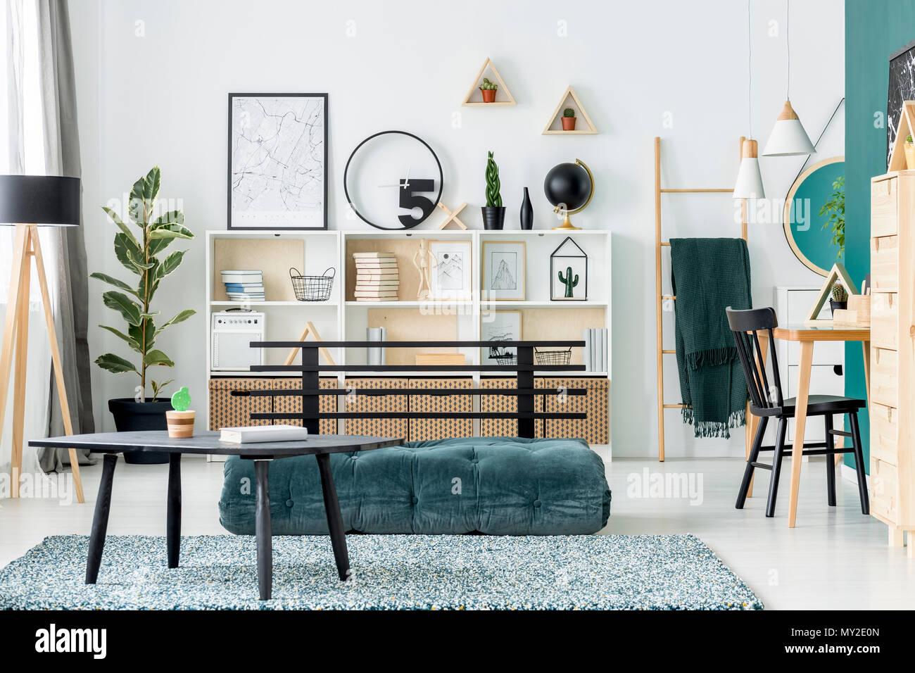 Black table on carpet near green futon in scandi living room ...