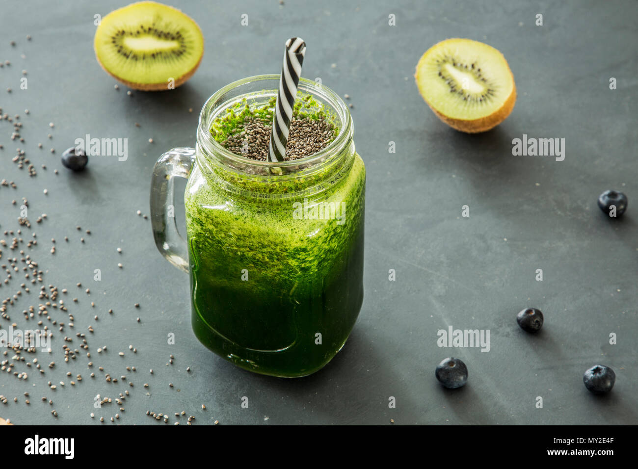 Green, healthy smoothie in a glass jar with a straw and kiwi, blueberries and chia seeds scattered around Stock Photo