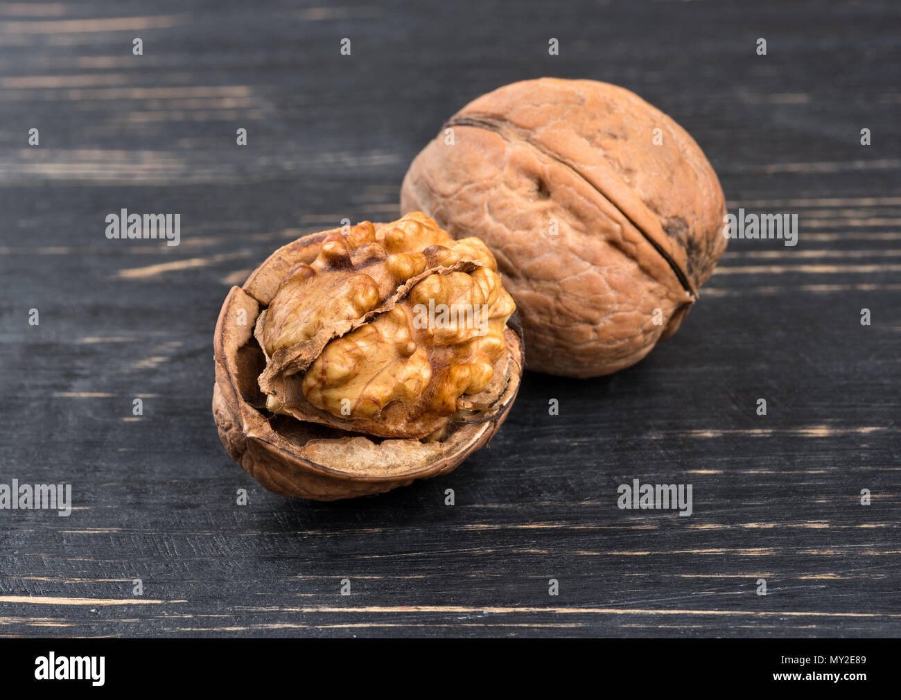 Two fresh walnut on wooden background closeup Stock Photo