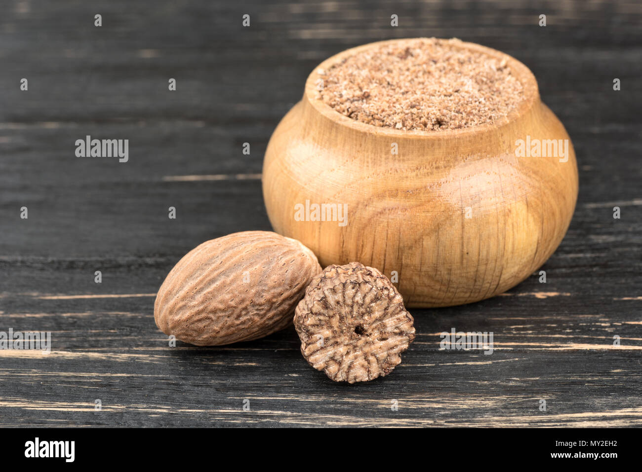 Jar with nutmeg powder and nuts on wooden background - Stock Image