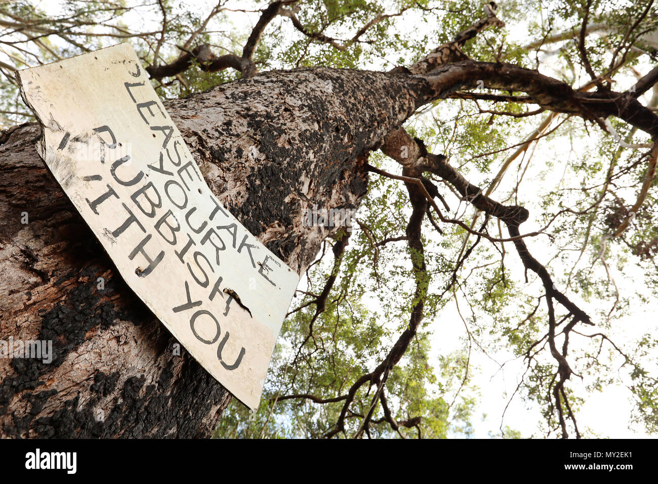 multiple views of an old worn sign post instructing campers fishermen bush walkers hikers to take responsibility for removing all waste trash rubbish  - Stock Image