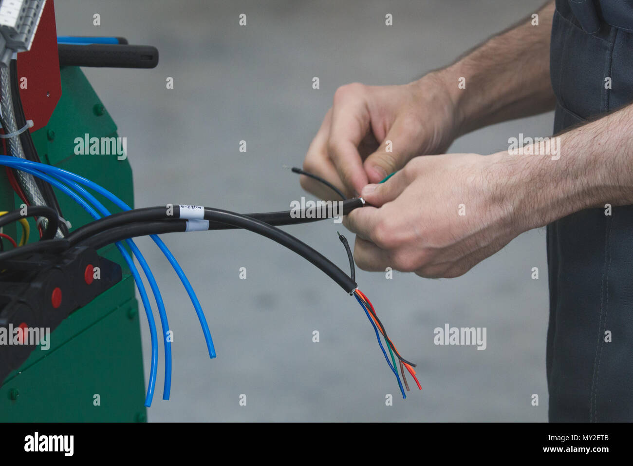 Hands of electrician works with electric wires - Stock Image