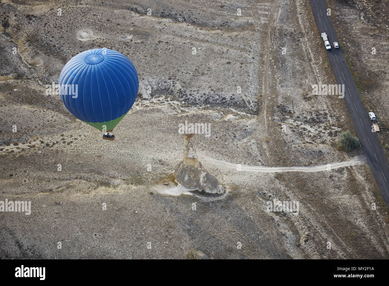 Blur hot air balloon flying over the road with motor transport. View from above - Stock Image