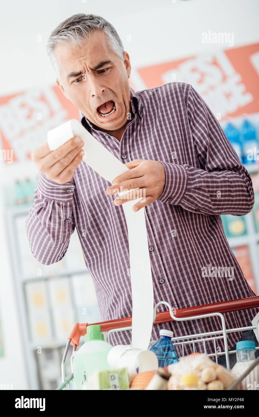 Man doing grocery shopping at the supermarket and checking a long expensive receipt, he is shocked and gasping - Stock Image
