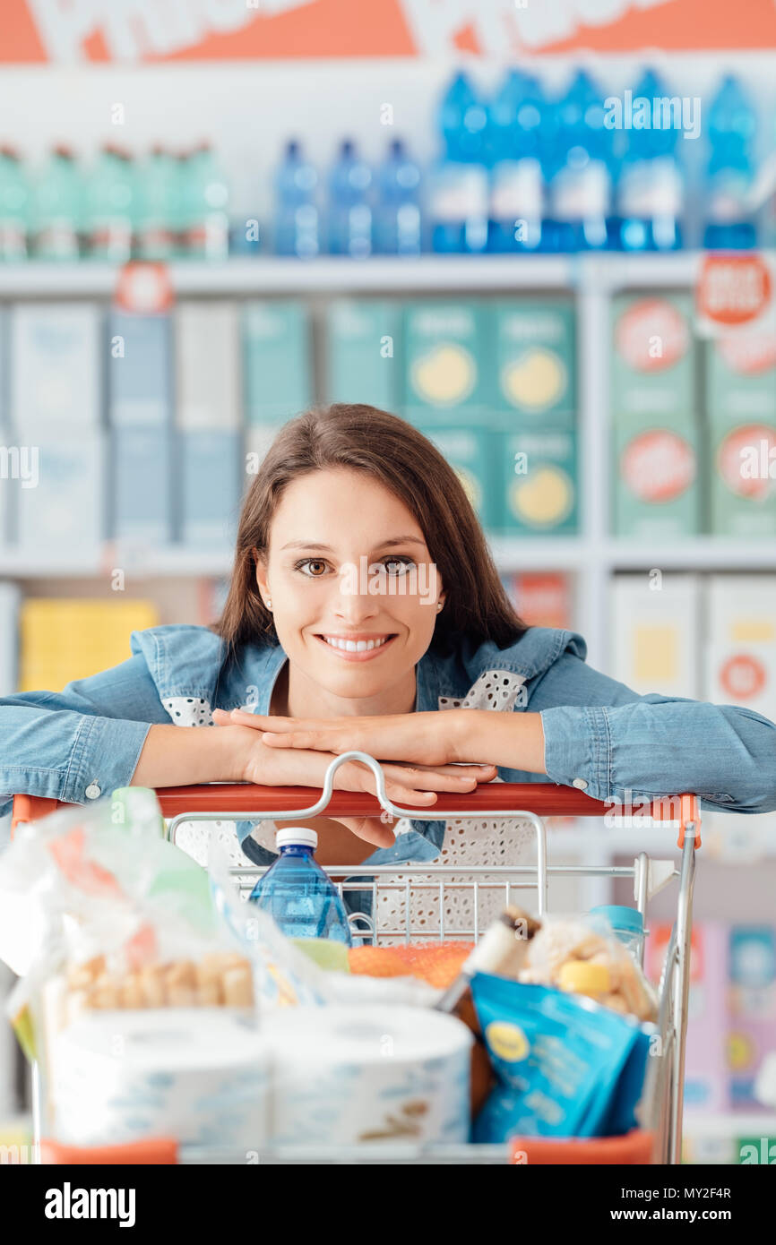 Smiling happy woman enjoying shopping at the supermarket, she is leaning on a full cart, lifestyle and retail concept - Stock Image