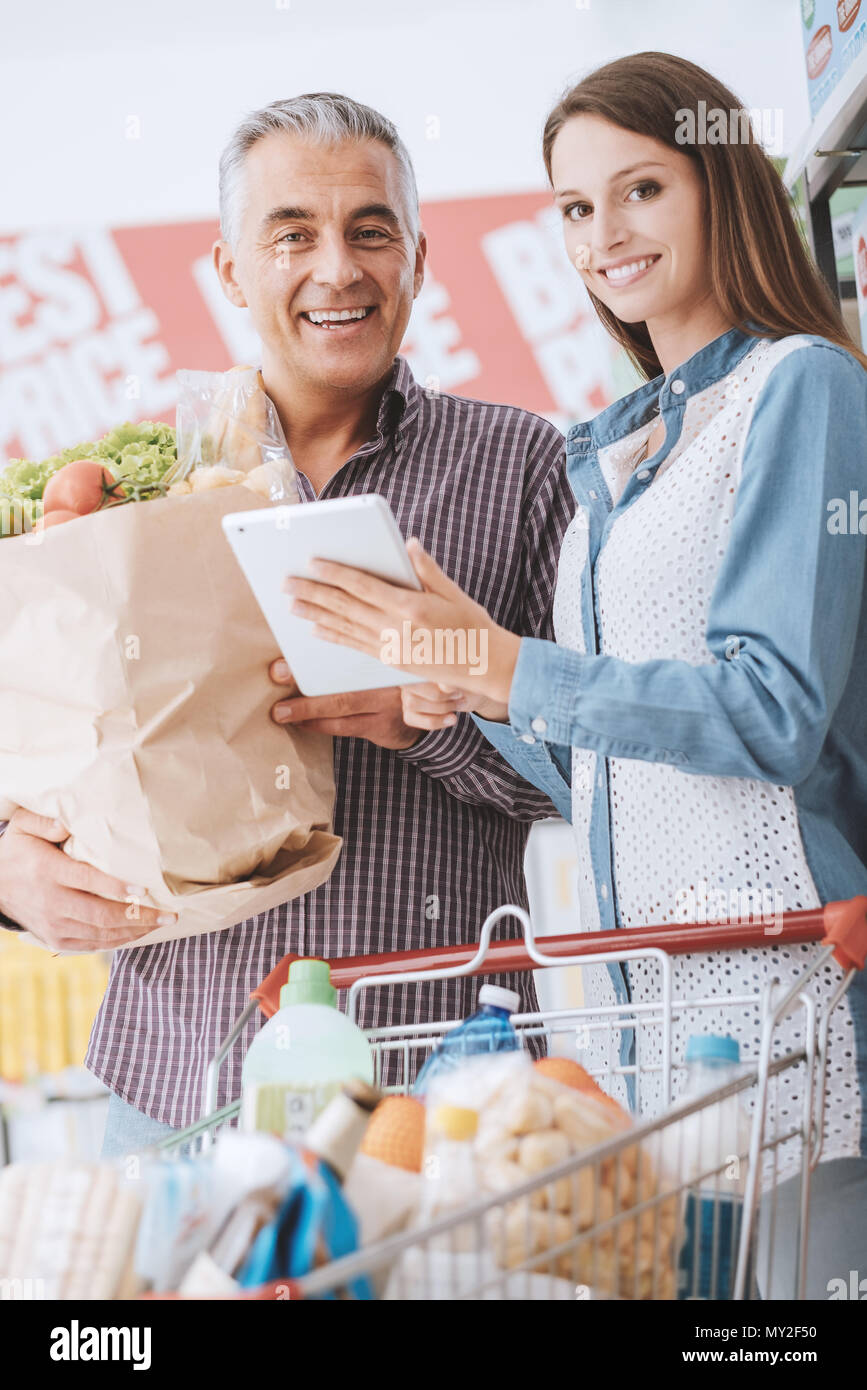 Happy family shopping at the supermarket, the man is holding a shopping bag and the woman is showing him products and discounts on the tablet - Stock Image