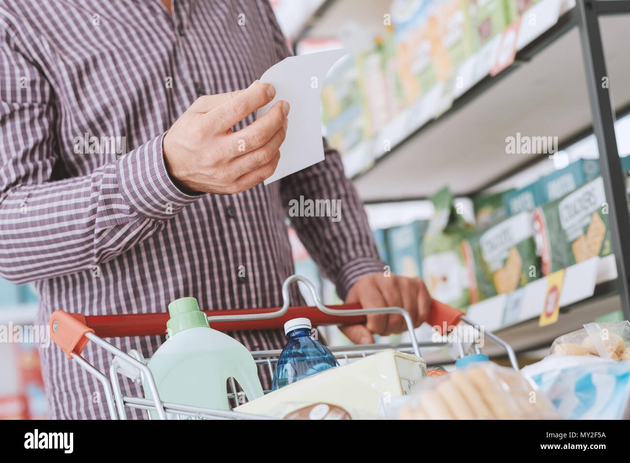 Man doing grocery shopping at the supermarket, he is pushing a cart and checking a list - Stock Image