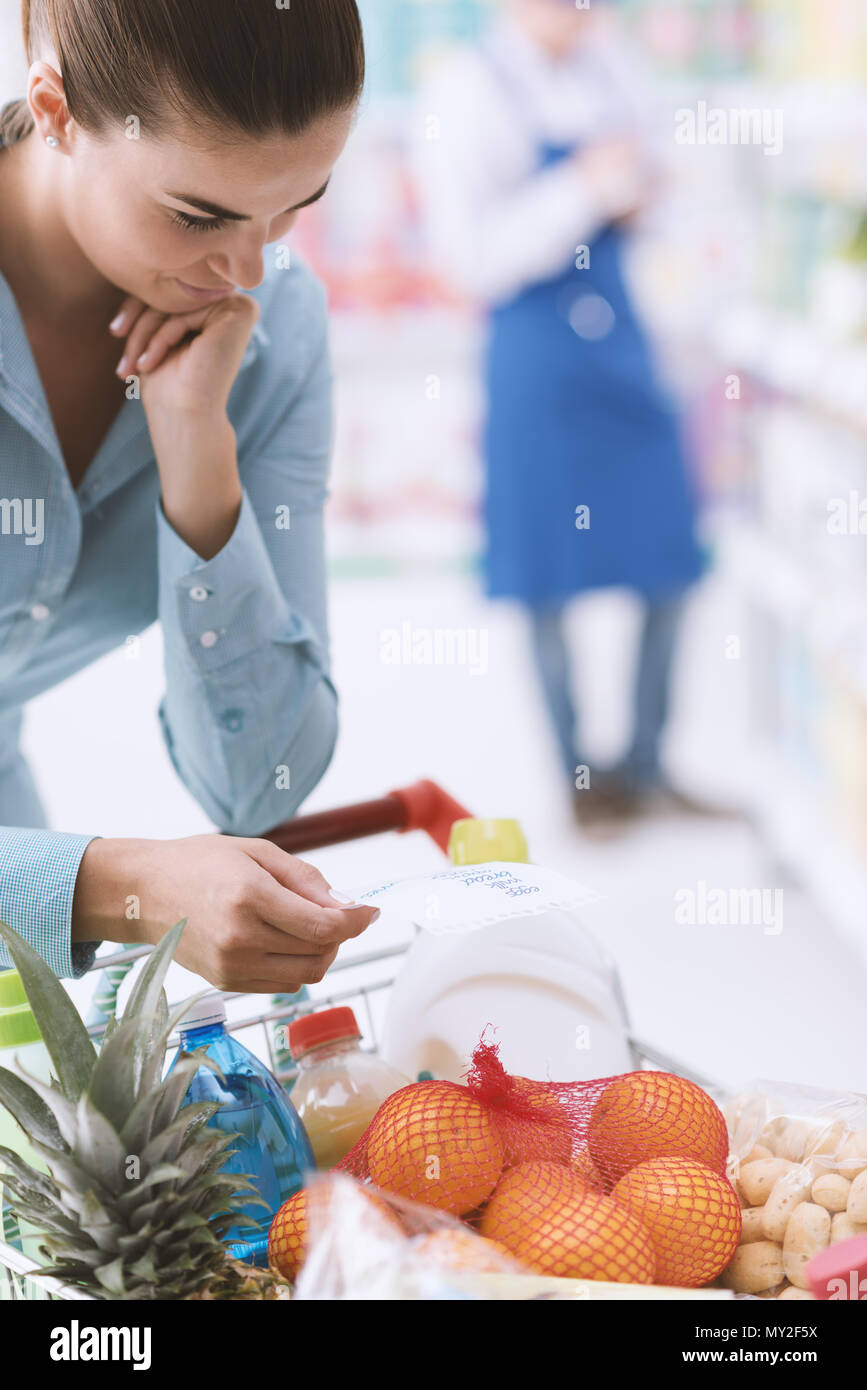 Woman doing grocery shopping at the supermarket, she is pushing a full shopping cart and checking a list - Stock Image
