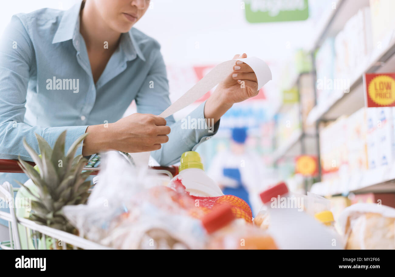 Woman shopping at the supermarket, she is checking a long grocery receipt and leaning on a cart, budgeting and lifestyle concept - Stock Image