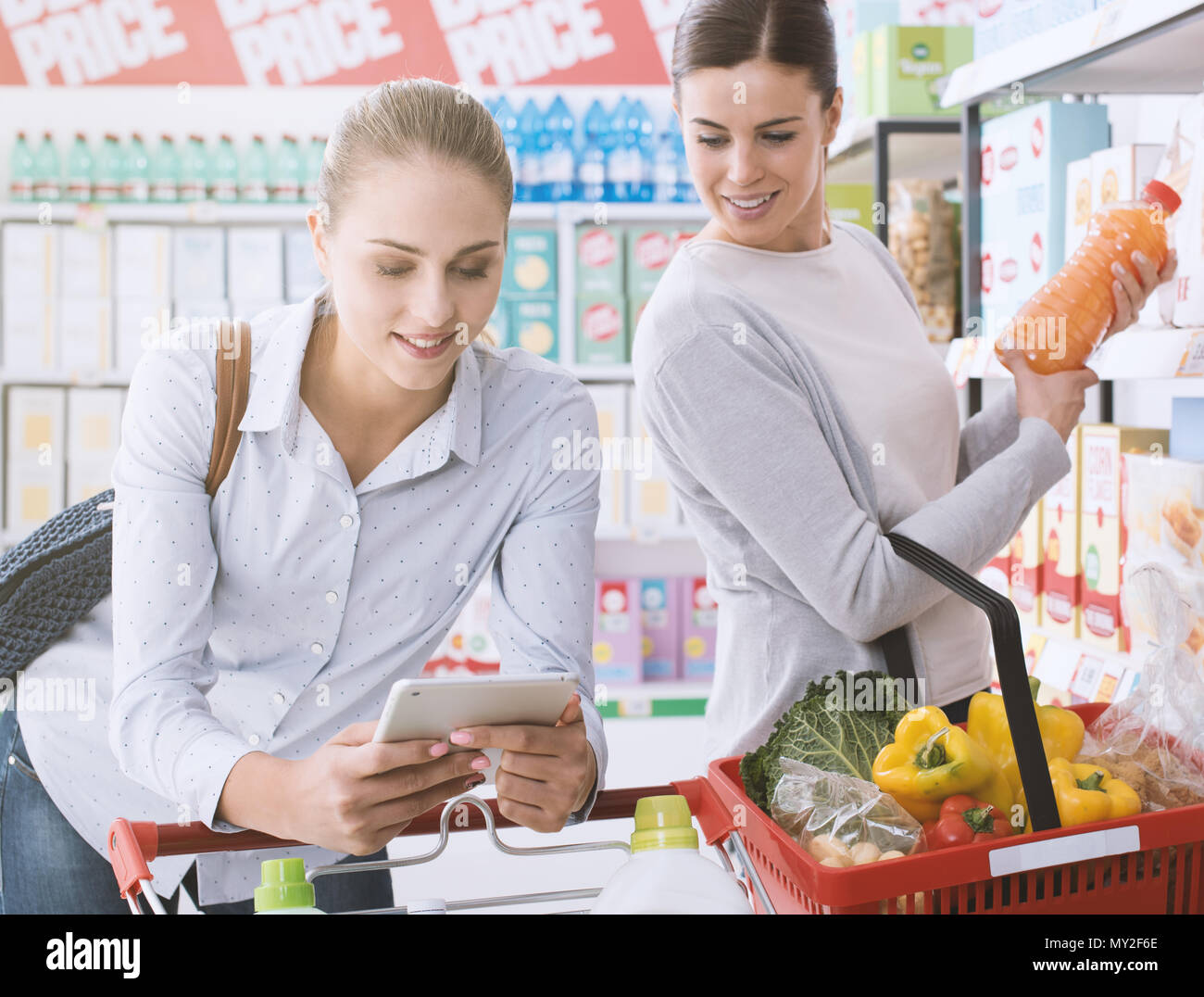 Happy female friends shopping together at the supermarket, they are connecting with a digital tablet, searching products and offers - Stock Image