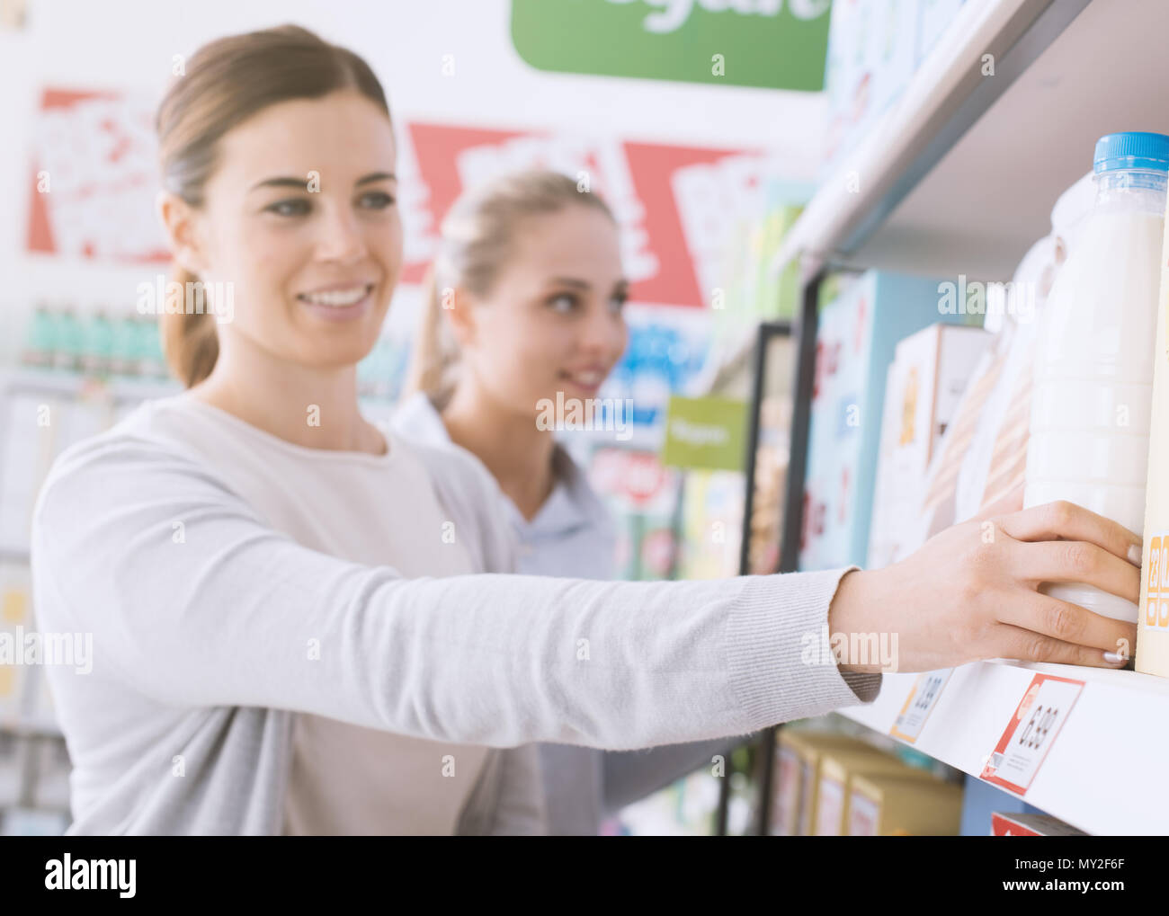 Happy women doing grocery shopping together at the supermarket, one is taking a bottle of milk from the store shelf - Stock Image