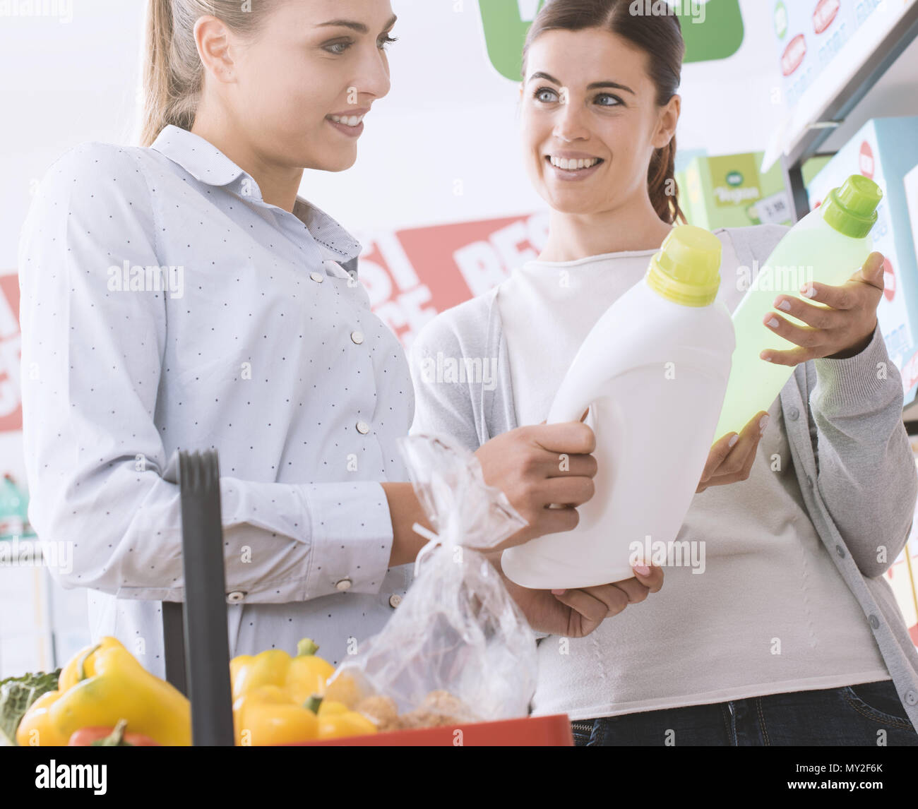 Women doing grocery shopping at the supermarket and choosing a laundry detergent, they are smiling and reading labels - Stock Image