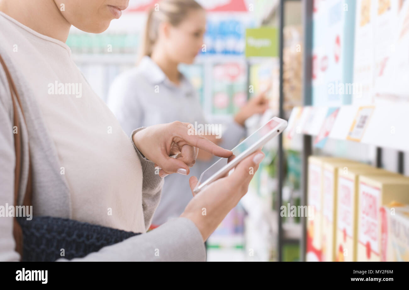 Young woman doing grocery shopping at the supermarket, she is searching products and discounts using her tablet, technology and marketing concept - Stock Image