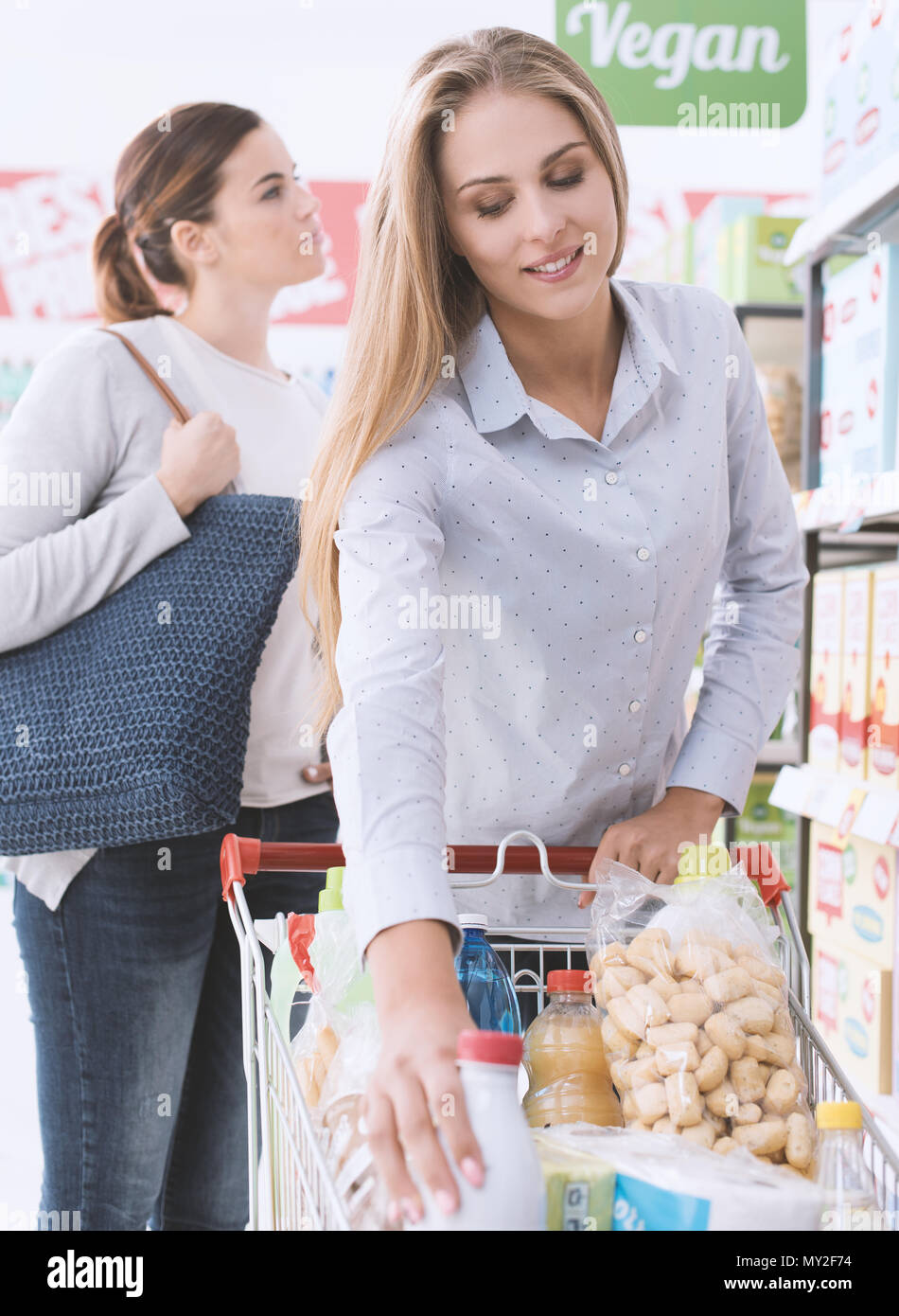 Friends shopping together at the hypermarket, one is putting products in the cart - Stock Image
