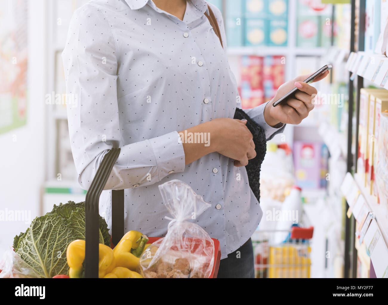 Young woman shopping at the store, she is using a smartphone and holding a shopping basket - Stock Image
