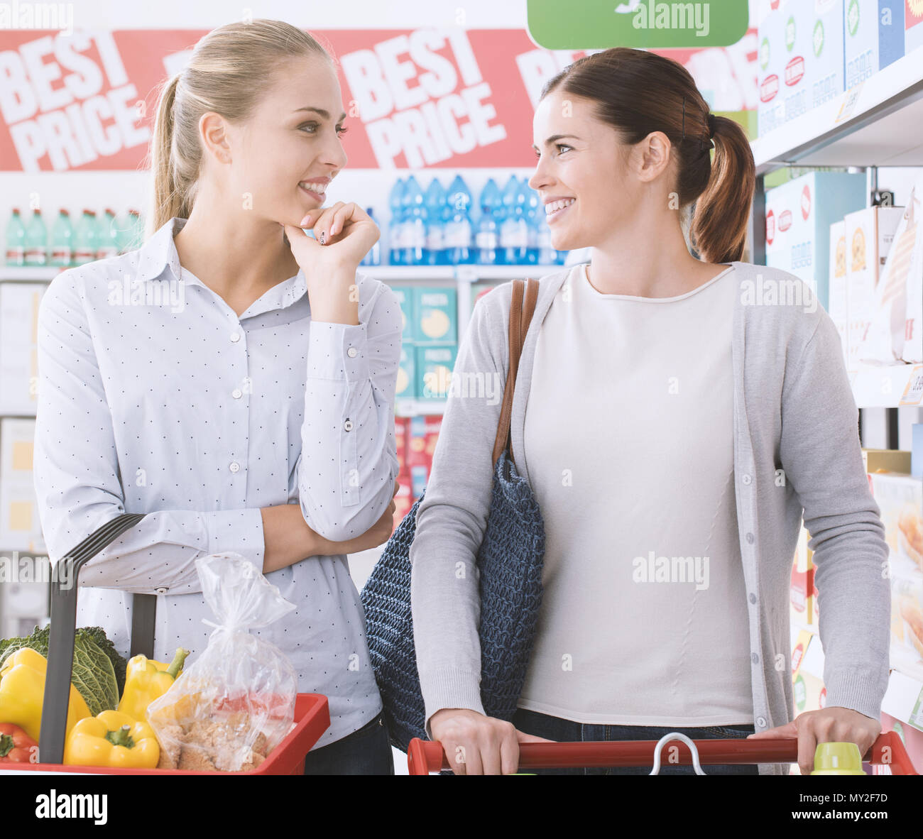 Happy women doing grocery shopping together at the supermarket, they are looking to each other and enjoying - Stock Image