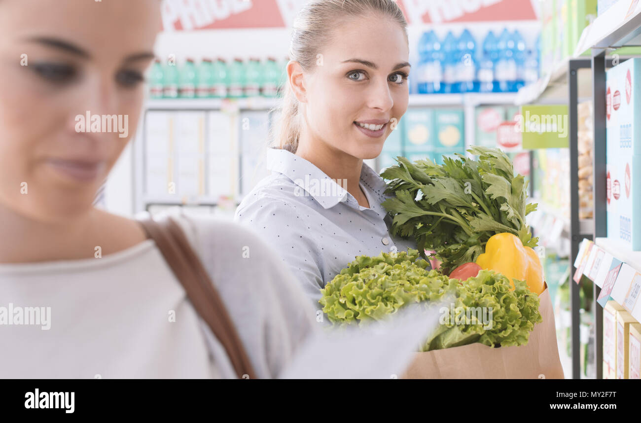 Friends doing grocery shopping together at the supermarket, one is holding a bag with fresh vegetables and smiling - Stock Image