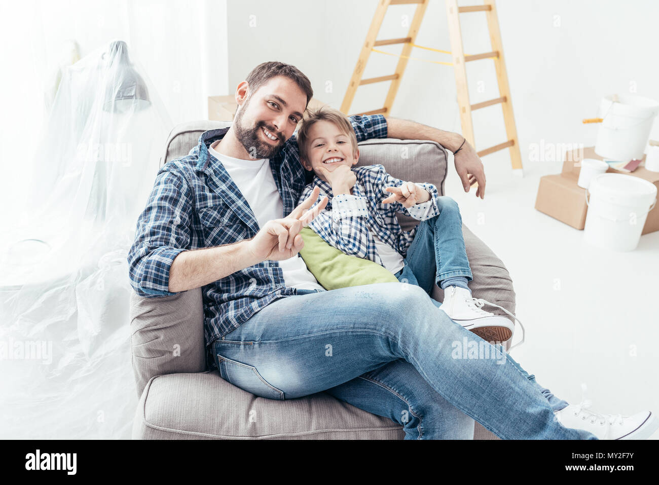 Smiling father and son relaxing on the armchair during home renovation, ladder, boxes and paint buckets on the background - Stock Image