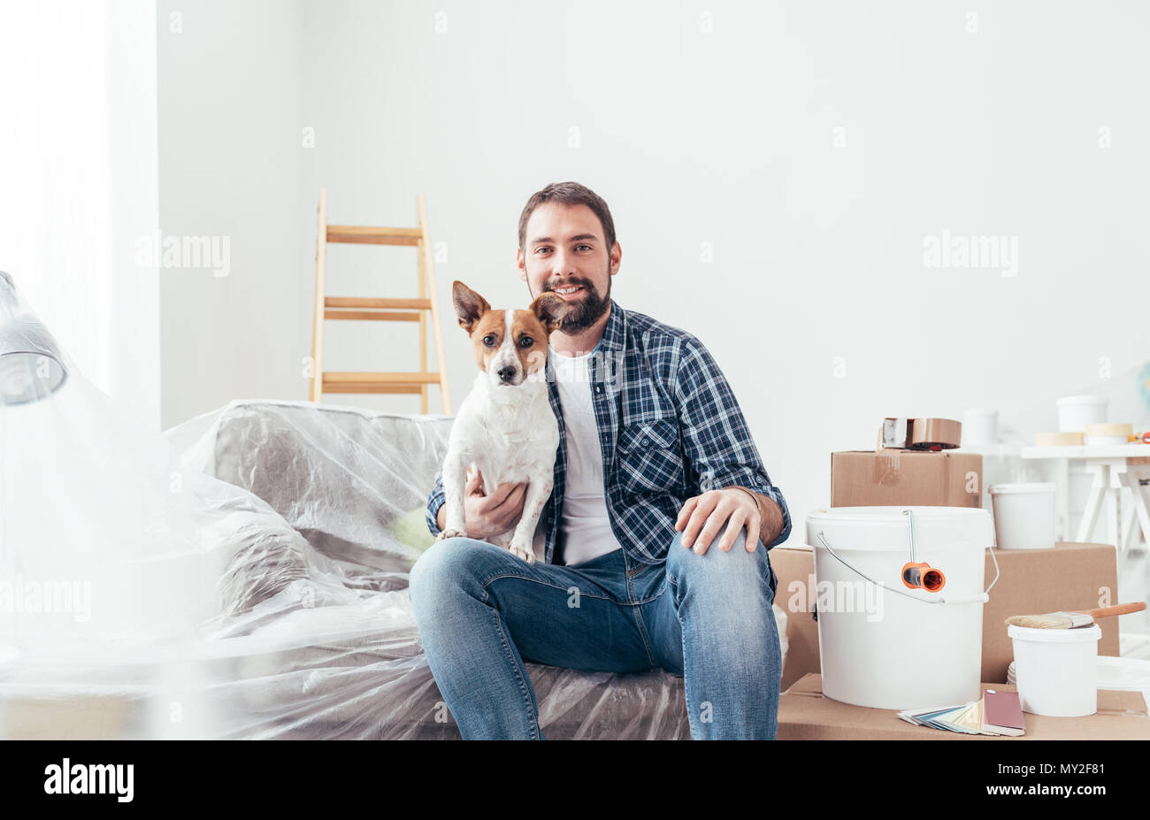 Happy dog owner posing with his pet in his new house during renovation, boxes and ladder on the background - Stock Image