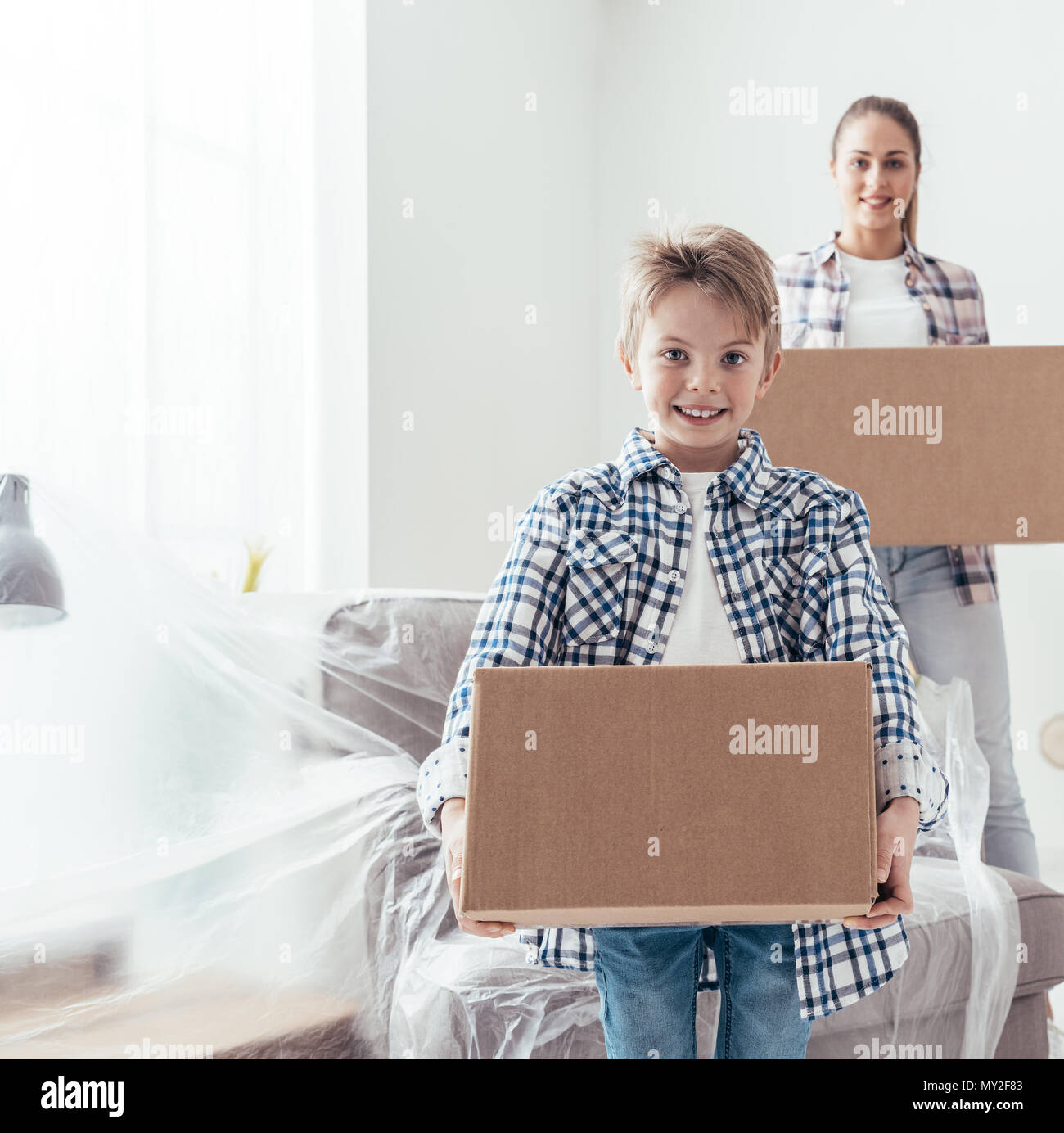Young family relocating and renovating their new house, they are carrying boxes, boy smiling on the foreground - Stock Image