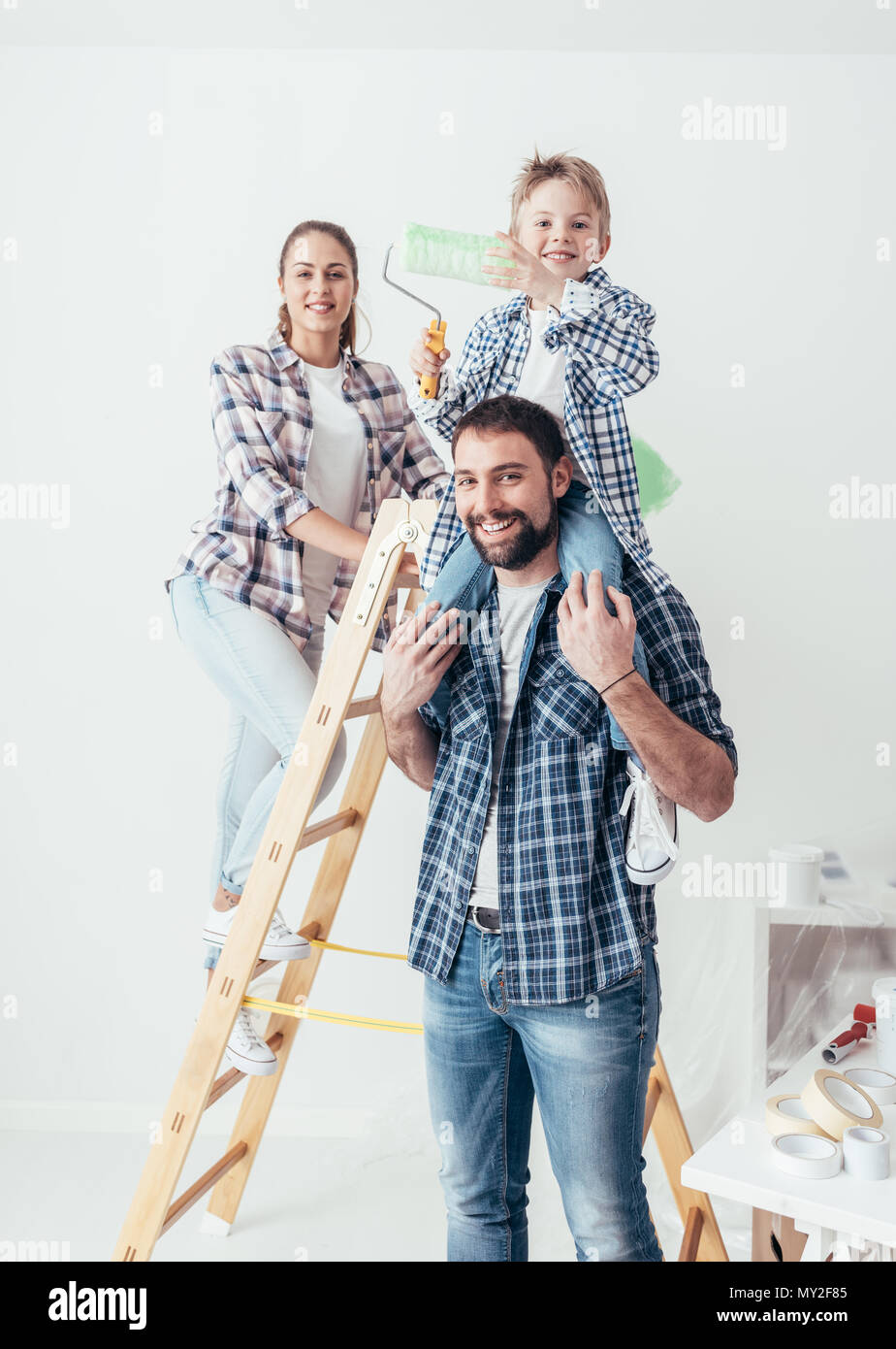 Happy family renovating their new home, they are posing together with a ladder and a paint roller, the father is piggybacking his son - Stock Image