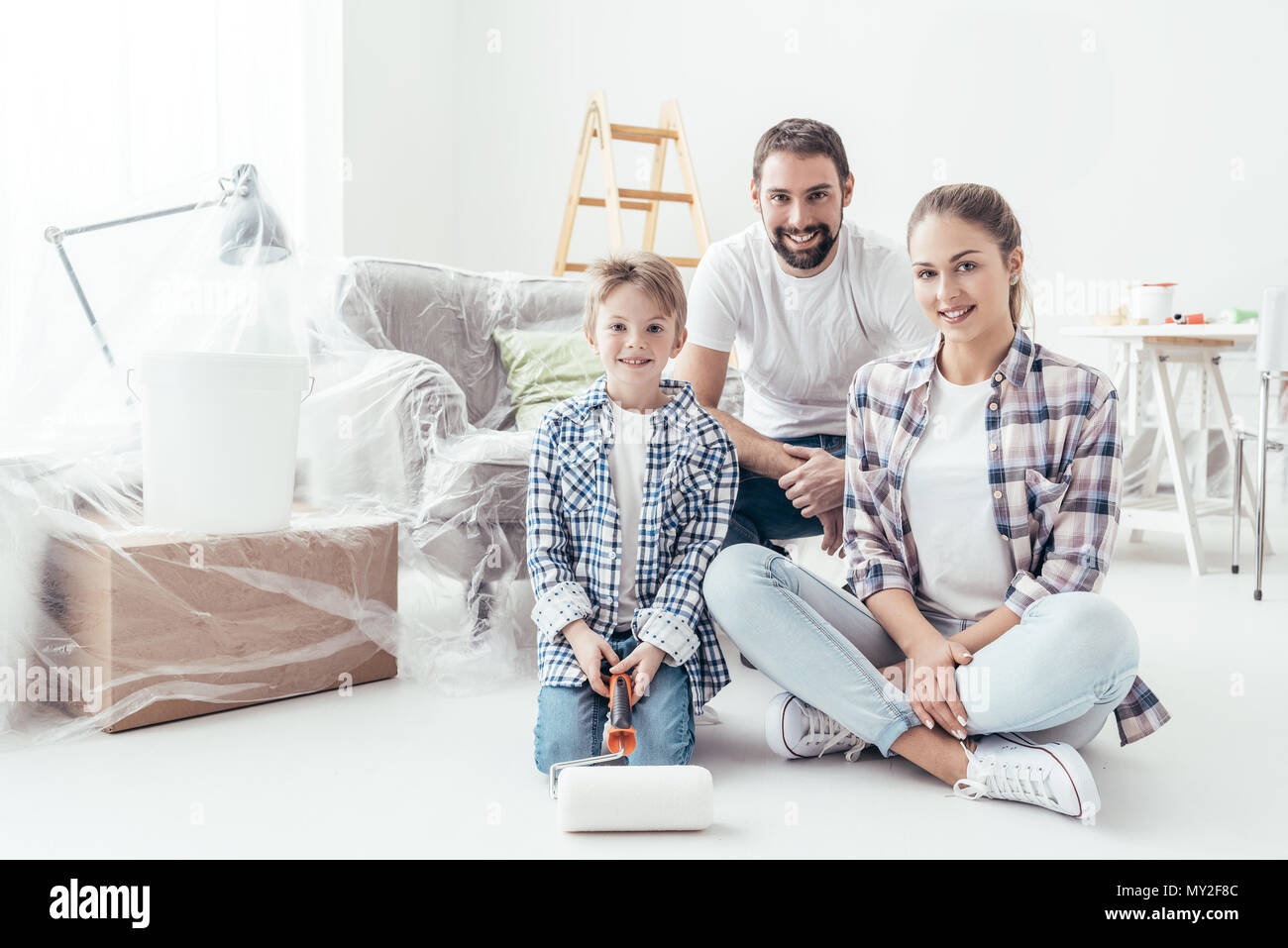 Home makeover, decoration and painting: happy family smiling and posing, the boy is holding a paint roller - Stock Image