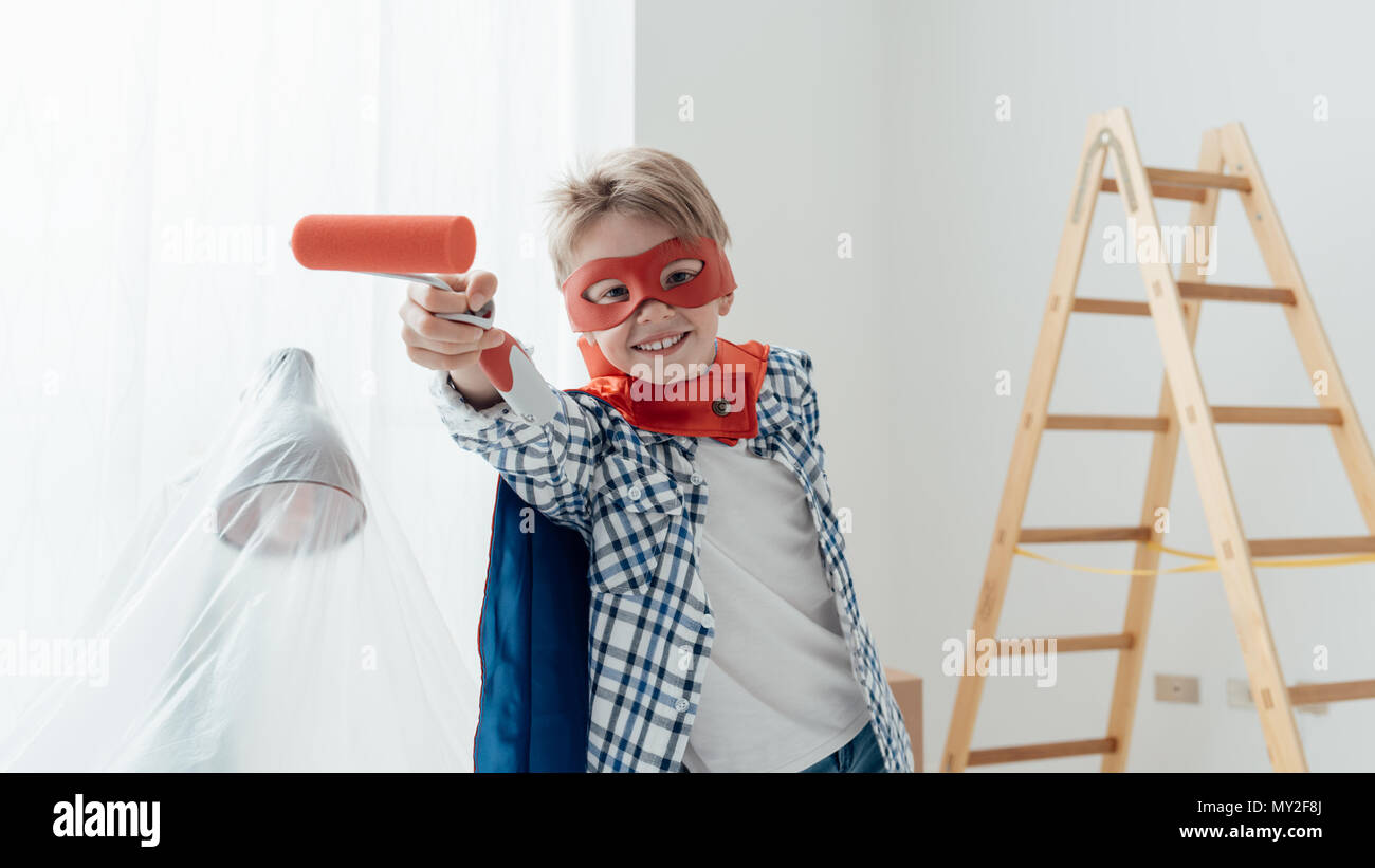 Cute superhero boy with mask and cape, he is holding a paint roller and smiling at camera, home renovation and diy concept - Stock Image