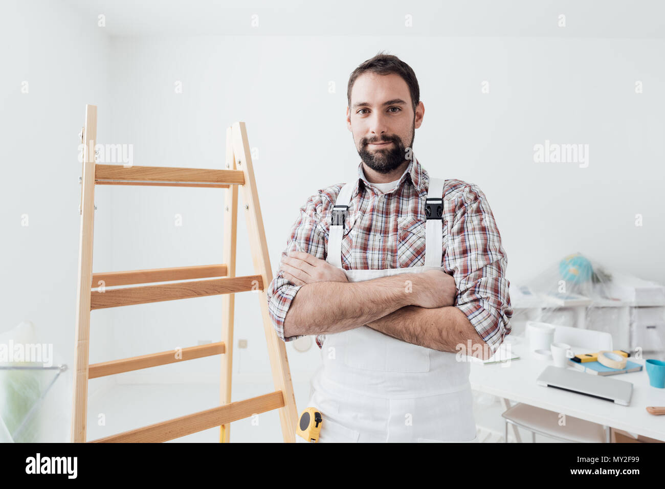 Confident professional painter posing with arms crossed, home renovation and decoration concept - Stock Image